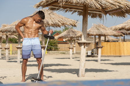 Sexy shirtless fitness model posing on the beach at the seaside.