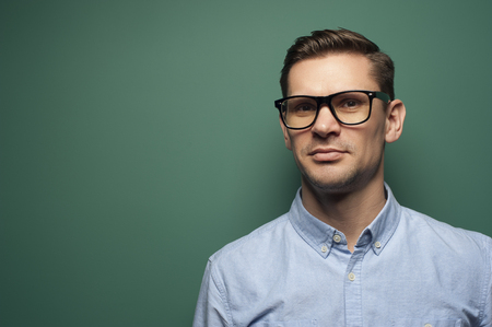 Young man businessman in a blue shirt and stylish glasses Stock Photo