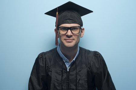 Happy portrait of young man student in hat of graduation Stock Photo