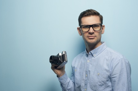 Young male photographer holding a new camera