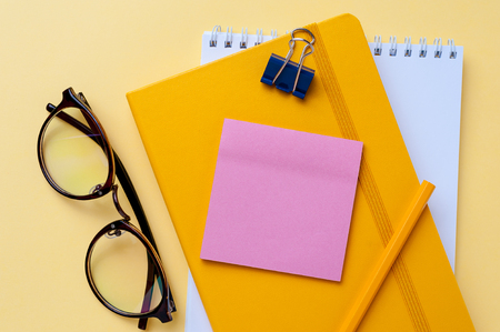 Empty notebook and office stationery yellow background.