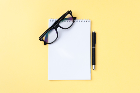 Notebook, eyeglasses and office stationery on bright yellow background