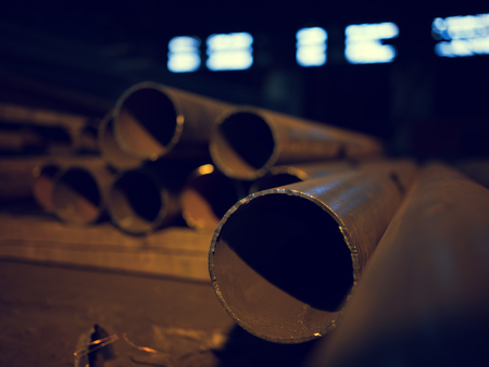 Close up of dusty old metal tubes on factory floor