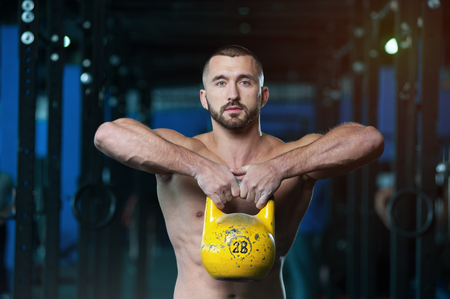 Shirtless Athletic Young Man Lifting Kettlebell in Hands.