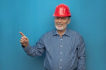 Elderly man in red helmet wearing blue shirt
