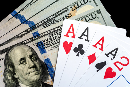 Four aces Playing Cards and Stack of 100 American Dollars Bills.