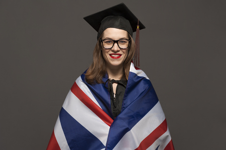 Charming female student smiling in eyeglasses wearing black mantle Banco de Imagens - 124609114