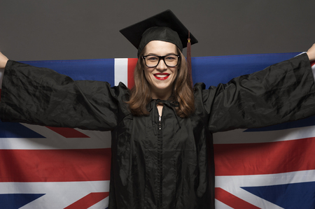 Charming female student smiling in eyeglasses wearing black mantle Banco de Imagens - 124609116