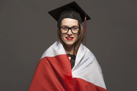 Charming female student smiling in eyeglasses wearing black mantle Banco de Imagens - 124609115