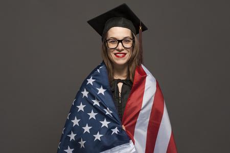 Charming female student smiling in eyeglasses wearing black mantle Banco de Imagens - 124609119