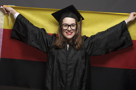 Charming female student smiling in eyeglasses wearing black mantle Banco de Imagens - 124621426