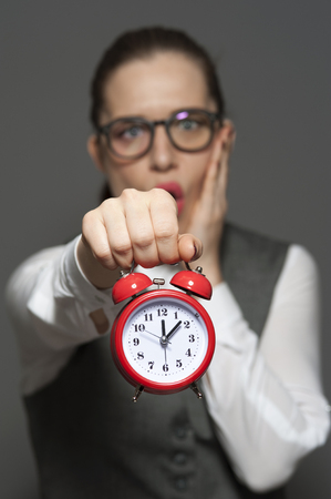 Nervous female office worker holding red clock