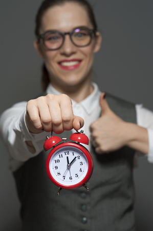Close-up of young businesswoman or office worker holding red clock in hands