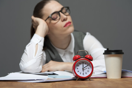 Tired office worker at the table with papers and red alarm clock