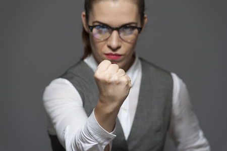 Angry unpleased attractive businesswoman looking at the camera showing fist