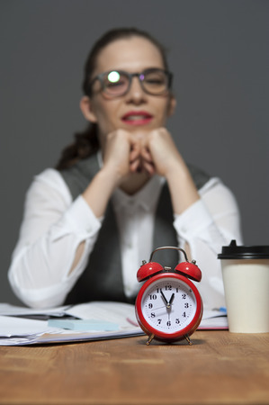 Business woman sitting to table with red alarm clock