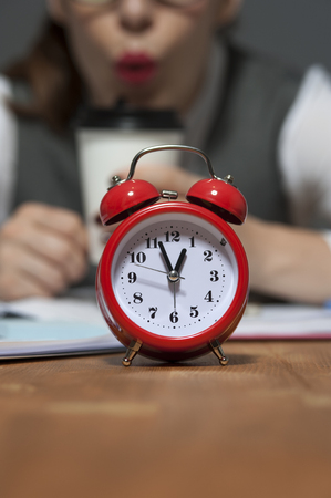 Red retro styled alarm clock on the background of blurry businesswoman