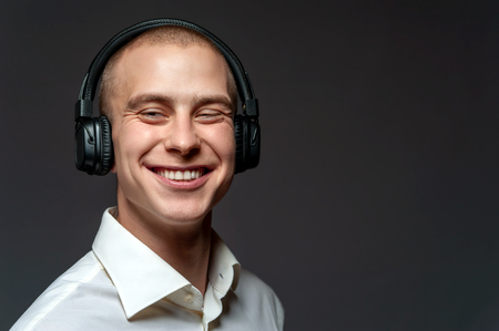 Smiling cheerful young guy with headphones