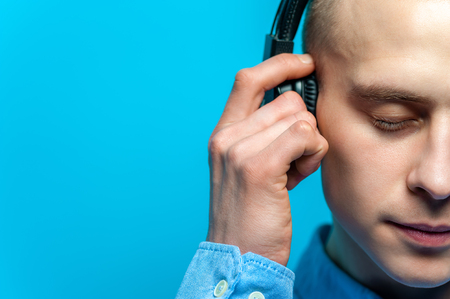 Close-up Portrait of a young handsome guy DJ in headphones and blue shirt posing against a blue background. Space for advertising