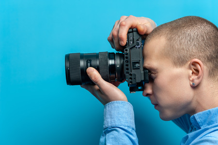 Male photographer examining his new camera