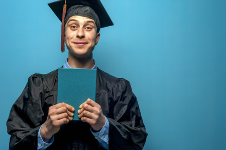 Happy cheerful Graduate man holding blue diploma