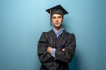 Male student graduate isolated on blue background