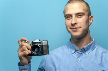Portrait of positive young male photographer holding vintage camera