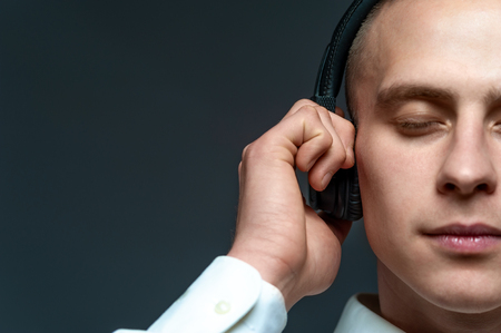 Young DJ guy listening to music in headphones Фото со стока