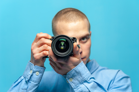 Young male guy photographer with dslr camera