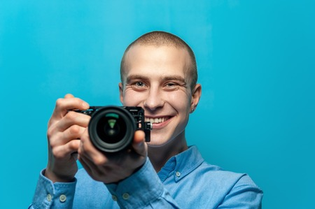 Portrait of positive young male photographer holding camera Фото со стока