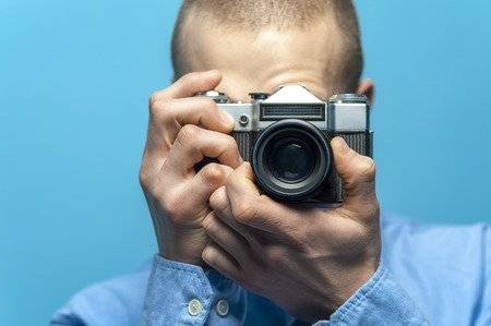 Portrait of young male photographer holding vintage camera