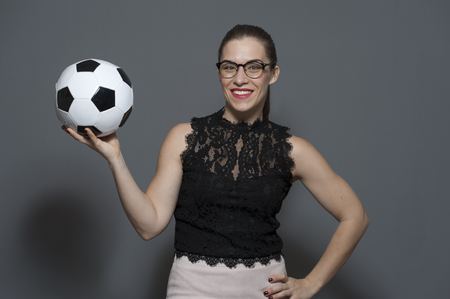 Young positive businesswoman - football fan holding soccer ball Фото со стока