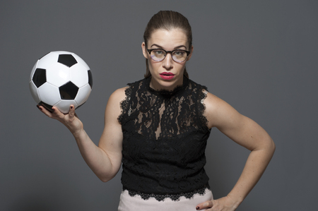Upset young businesswoman - football fan holding black and white soccer ball in hands Фото со стока