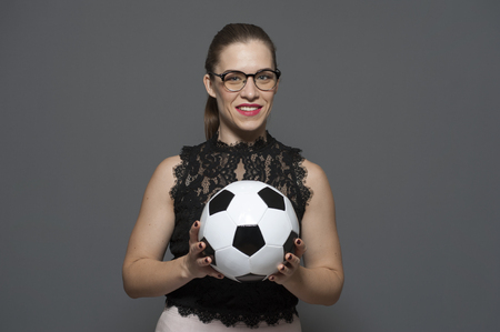 Young charming businesswoman - football fan holding soccer ball Фото со стока