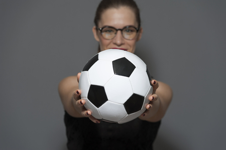 Young charming woman football fan or player holding soccer ball in hands