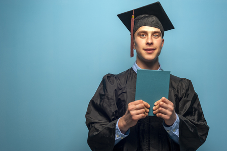 Graduate male student wearing black mantle and mortarboard Фото со стока
