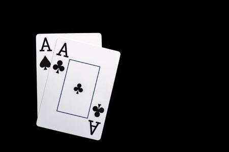 Two aces playing cards on black table