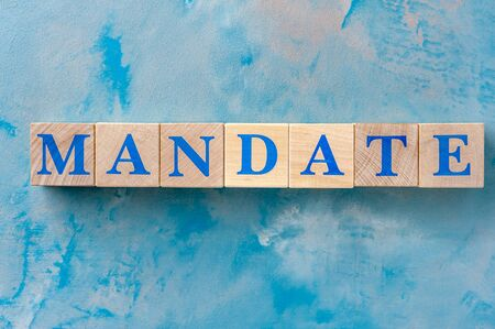 Wooden cubes with word MANDATE on blue table.