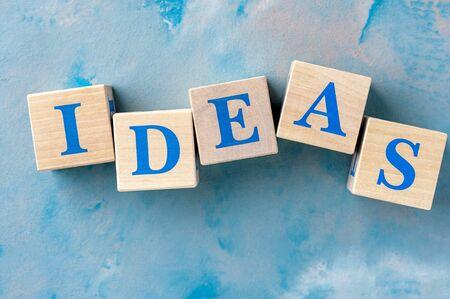 Holzwürfel mit Wort IDEAS auf blauem Tisch.