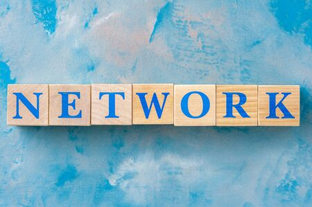 Wooden cubes with word NETWORK on blue table.