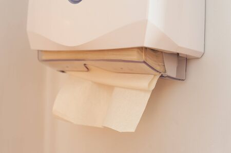 Close-up of paper towels in a dispenser hanging on the wall