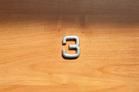Table number three hanging on a wooden door Stok Fotoğraf