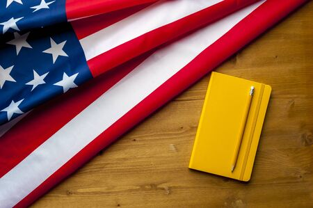 Top view flag of United States of America notebook and pencil lie on a wooden table. The concept of finding information and obtaining a residence permit. Advertising space