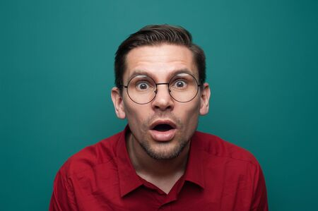 Portrait of shocked surprised young man in glasses