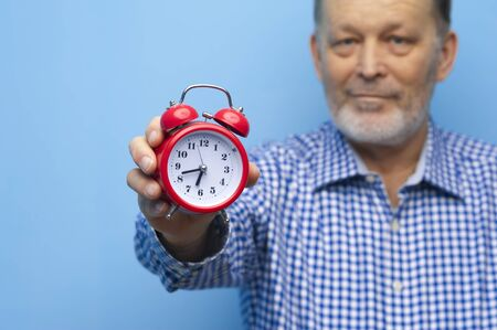 Elderly man in eyeglasses with a little red clock Stock Photo