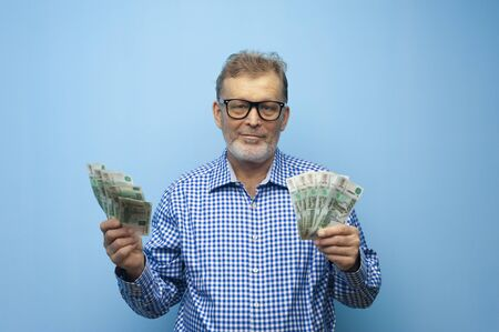 Elderly man in eyeglasses holding fan of rubles