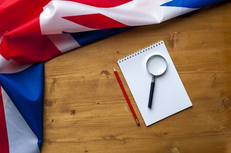 Top view flag of United Kingdom with notepad, pencil and magnifier lie on a wooden table. The concept of finding information and work in the country. Advertising space