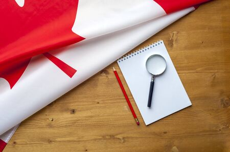 Top view flag of Canada notepad pencil and magnifier lie on a wooden table. Place for advertising. Concept of searching for real estate information in the country