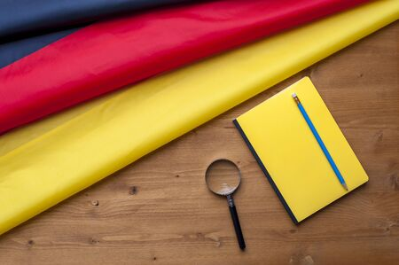 Top view of the flag of Germany lies on a wooden table next to a notebook with a pencil and a magnifier. Concept of job search and visa. Advertising space Stock Photo