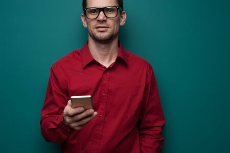 Portrait of a positive young man in glasses with phone